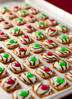 These sweet and salty treats are made from pretzel squares, Hershey's Hugs kisses and red and green M&Ms. That's it! Put one kiss on top of each pretzel square. Heat in a 200 degree oven for about 4-5 minutes, just until shiny and soft (NOT melted). Remove from the  oven and place one M&M in the center of each treat. Press down on the M&M until the kiss is spread out across the pretzel. Refrigerate for about 5 minutes before serving.