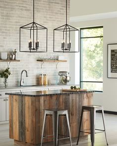The transitional Perryton pendant light collection by Sea Gull Lighting is inspired by stately, carriage light lanterns. In addition to the large pendants shown here as kitchen lights, there's a small pendant and an island pendant. Damp rated,