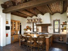 This kitchen features unique elements such as a brick barrel vault ceiling, large center island, iron chandelier and classic white stucco hood vent.