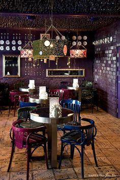 Stunning bohemian luxe cafe interior design. Dark mauve walls, hanging utensils and grassy roof with splashes of silver and gold.