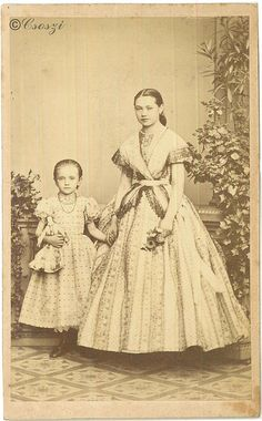 1860 Young girls. Older girl still doesn't cover her hair and skirt hasn't reached the floor yet, but her dress pattern is similar to that worn by adults. Younger girl has no crinoline under her skirt and widely set small polkadots