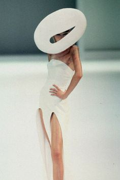 This picture uses the constrained visual language. The woman wears a very simple white dress and a white strange hat. The hat has a nice line and shape, but looks high fashionable. The dress is not created with the service reservoir. It has streamline cut to show the beauty.
