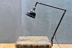 USA, c.1930s. Vintage Industrial Black Enameled Drafting/Drawing Vise Clamp-On Articulate Lamp. All Original, with Original Finish and Bell Shade and down to the Cord. Long Arms, a Great Find, Lots of Wear to Enamel and Patina to all Surfaces.    Segmented Arms Bottom to Top Lengths: 20, 19 and 10 in. *(Bell Dia: 6 in.)