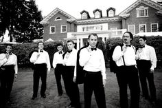 black and white photo of groomsmen with groom, with tuxedo jackets slung over their shoulders - photo by Seattle based wedding photographers La Vie Photography