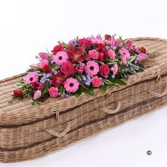 This bright casket spray feautring a classic selection of flowers in pink, red and lilac includes large-headed Rose, carnations, Gerbera and Oriental Lily complemented by luxurious foliages.