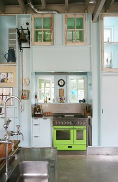 This eclectic pale blue kitchen, in converted garage, has high unfinished ceilings, refurbished windows, beautiful stainless steel sink and hot lime green stove. Click through for more photos of this Dutch design firm's office space.
