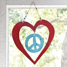 "Handmade by artist Jes MaHarry and her husband Patrick Henderson, this work of ""heart"" welcomes all who enter your home with a message of love and peace. Handcut, handpainted steel hangs from leather cords strung with colorful trade beads. Signed by the artists and made in the USA. Approx. 10""W x 11""H."