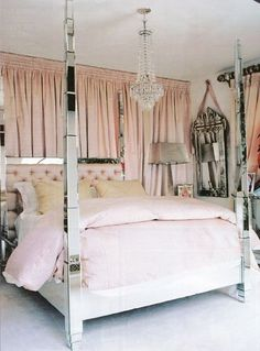 Mirrored bed with chandelier and light pink draperies and linens bedroom