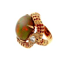 Rare 20.18ct. Black Fire Opal. Wrapped Around the Year of the snake.. With Orange Saphires, and Brown Diamonds and crowned with a trap Diamond on the Head of the snake. All stetted in 18kt. Rose Gold.