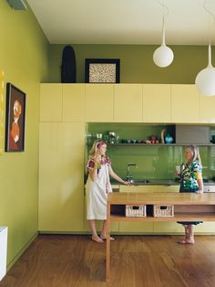 """Lime green walls complement this """"eccentric, multifunctional, personal sanctuary"""" while a pair of white ball pendant drop lights add height.  Photo by: Prue Ruscoe"""