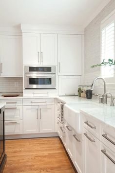 Brilliant kitchen features white shaker cabinets paired with Luminous Calacatta Marble and a white linear tiled backsplash under light gray grasscloth wallpaper framing window over a farmhouse sink paired with a gooseneck faucet as well as a built-in microwave nook beside a small kitchen appliance garage.