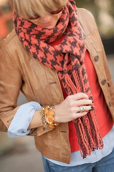 A cute fall outfit, a leather jacket with a colored sweater and an oversized scarf paired with a few gold bracelets
