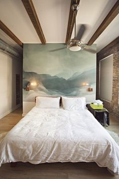 quarto de casal com piso de madeira, parede com tijolos a vista e painel decorativo na cabeceira da cama