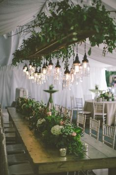a pretty gathering table greenery chandelier