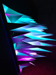 « Primary » by Flynn Talbot, 3D triangles light sculpture in cardboard with 3 sources of LED lights playing with shadows and colors.
