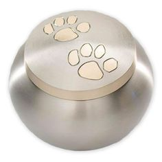 With its brushed, pewter-colored finish and whimsical paw prints decorating its lid, this brass pet urn is a beautiful tribute to your cherished friend.