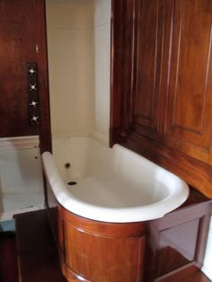 Late 19th century, cast iron bath with overbath shower.  Controls to the left of the shower hood, with small holes set vertically in  lines, and evenly spaced in a semi-circle.  Walnut wood splashback with curved bath panel.  Lady Ailsa's Dressing Room, Culzean Castle.