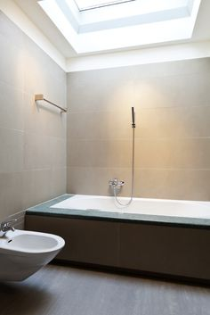 Large White Soaking Tub With Handheld Showerhead And Towel Rack