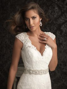 "Allure Bridals wedding dress, style 9010. ""This beautiful style is created from a rich lace appliqué on soft net. The sculpted neckline features scalloped cap-sleeves that are adorned with pearls and Swarovski crystals."""