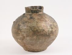 Persian, circa 10th century AD. A pottery urn of globular form with an elongated cylindrical neck, having remnants of polychrome on interior and exterior including metallic copper and applied iridescence.
