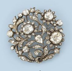 A ROSE-CUT DIAMOND BROOCH, BY ROZENDAAL Of openwork circular form, composed of plants and flowers set with rose-cut diamonds, Dutch, early 20th Century, maker's mark JR3