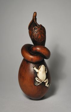 An unusual netsuke of a long-necked boxwood gourd upon which rests an ivory 'Kaeru' frog. The double gourd is a symbol of abundance throughout the Far East, and the frog has long been a symbol of good luck,