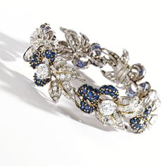 Platinum, 18 Karat Gold, Diamond and Sapphire Bracelet, Circa 1960 The flexible strap composed of links of foliate design set with 6 larger round diamonds weighing approximately 12.00 carats, further set with small round diamonds weighing approximately 16.00 carats, accented by round sapphires, length 7½ inches.  With box signed Louis Feron.