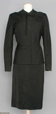 1940s ADRIAN BLACK SKIRT SUIT, Wool gabardine, jacket pieced w/ curved panels, 2 pocket flaps just below each shoulder, self covered buttons, string bow at collar