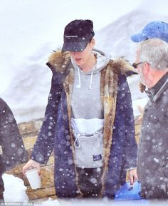 She looks chilly! Keeping her head warm was a simple black baseball cap and she donned silver hoop earrings