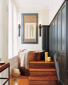 A copper, Japanese-style soaking tub is set into a platform built three steps up from the bathroom floor. The floor and stairs here are made of walnut, suggesting a total change of environment from the cool surfaces in the rest of the room. Featured in: A Bathroom Soaking in Style   - ELLEDecor.com