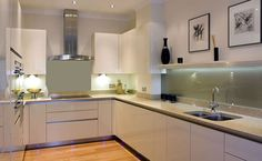 View into u-shaped kitchen with handle-less Magnolia High Gloss furniture and Ivory Coast Silestone worktops. Left of centre, Neff induction hob, beneath Neff extractor hood in stainless steel centred on back wall of kitchen. To left of image, tall units, housing Neff ovens and warming drawer. To right of image, base units only, with long glass splashback and narrow shelf above. Stainless steel effect plinth at floor level, with tiny inset LED lights, and oak flooring.