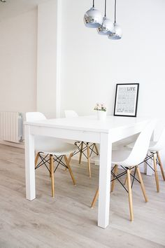 three silver pendant lights over simple white dining room table