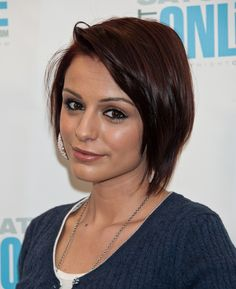 This is a great haircut for someone with fine, thin, and straight hair and who is looking for something modern, short, and easy care. A cowlick up front causes the strands to flip and swirl but one can use this as an asset as we can see here. Her color is a berry brunette with a hint of red that is barely noticeable and not streaky. She is sporting a side part and strands go up and over to keep an open forehead.