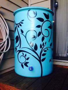 """Rain Barrel"" I used spray paint and wall decals. Its my condo water resource - I fill it with water so I don't need to run a hose from my bathroom everyday to water my garden. Not yet sure if the decals will survive the outdoors."