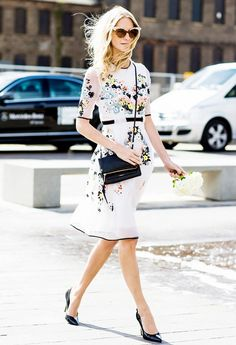 Poppy Delevingne in floral dress, black cross body bag, black pumps, and metallic cat-eye sunglasses