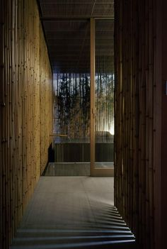 Hot spring screened with a wall of vertical bamboo poles featuring a bamboo spout for the water.