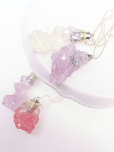 "Rock crystal pendants filled with holographic glitter that light up! Twist the pedant sideways for it to glow. Handcrafted in assorted colors measures 2"" Handmade in NYC"