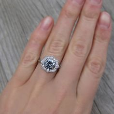 Grey Moissanite Engagement Rings To Obsess Over ~ Dark Grey Moissanite Engagement Ring with Diamond Halo + Band with Twig and Leaf motif, dotted by a tiny diamond on either side in White Gold