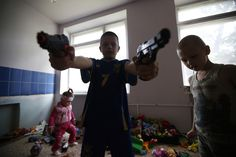 Image 24 of 35: Children of families who have fled from fighting in Slaviansk play with toys at temporary accommodation in a dormitory in the town of Ilovaisk in eastern Ukraine June 3, 2014.REUTERS/Maxim Zmeyev