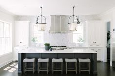 Five gray backless stools sit beneath a white quartz countertop contrasting a long dark gray wainscot island and fitted with a farmhouse sink with a polished nickel deck mount faucet illuminated by two Urban Electric Co Urban Bell Lanterns.