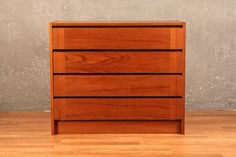 Handsome and warm teak 4-drawer commode with a simple and sleek danish modern design. A great-size piece for your extensive fashion collection. In good condition with some veneer chipping. Dimensions: 31.5 w 15.5 d 26.5...