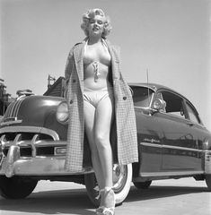 Marilyn Monroe in a two piece swimsuit posing next to a Pontiac Chieftain on the backlot of 20th Century-Fox in 1951   StyleCaster