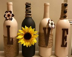 Wine bottles that have been hand painted wrapped with jute twine and decorated in a unique style. Colors are black and beau comb beige Glass Bottle Crafts, Wine Bottle Art, Painted Wine Bottles, Lighted Wine Bottles, Diy Bottle, Crafts With Wine Bottles, Alcohol Bottle Crafts, Wine Bottle Centerpieces, Bottle Candles