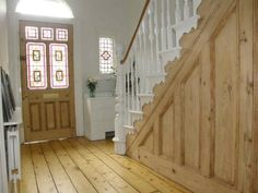 Stained glass front door, wooden floor and white bannister