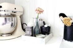 white kitchen with a classic stand mixer the colour of vanilla ice cream, and a plain canister painted matte black...