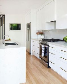 A white quartz waterfall island is fitted with a white quartz countertop holding a stainless steel dual sink beneath a modern polished nickel faucet.