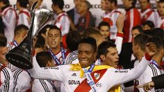 River Plate's Teofilo Gutierrez of Colombia holds the trophy as players celebrate on the podium winning the Argentine league soccer cham...