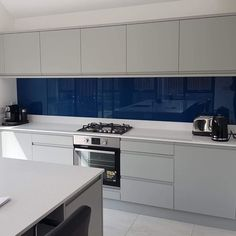 Stunning Inky Blue glass Splashback- a perfect contrast to this kitchens light grey cabinets, and white work surfaces. Kitchen Wall Colors, Diy Kitchen Decor, Kitchen Interior, Kitchen Ideas, Design Kitchen, Kitchen Inspiration, Kitchen Soffit, Glass Kitchen, Kitchen Cabinetry