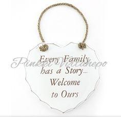 """Kaunis sydämenmuotoinen kyltti, jossa teksti """"Every family has a story, welcome to ours"""". Kyltin saat roikkumaan haluamaasi paikkaan punotusta narusta.  Koko: korkeus 17cm"""