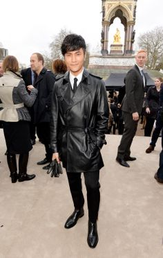 Chinese actor Chen Kun wearing a black Burberry trench coat at the Prorsum Menswear A/W14 show in London